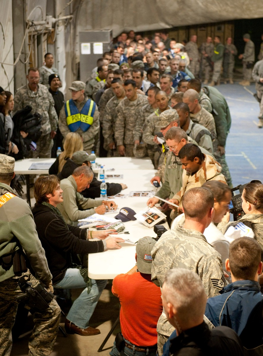 The line-up of troops to get autographed photos and meet with the touring group snakes outside the building.  (USO Photo by DAVE GATLEY)