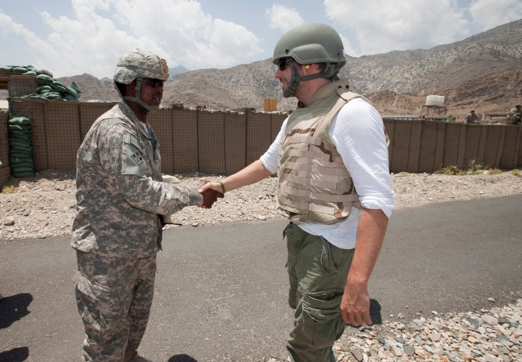 Actor Bradley Cooper greets a soldier at a remote forward operating base as part of a seven-day summer USO tour to the Persian Gulf to boost troop morale in 2009. (USO Photo by Fred Greaves)