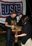 Country music star Craig Morgan autographs a guitar for a child after a concert he performed at Anderson Air Base in Guam December.