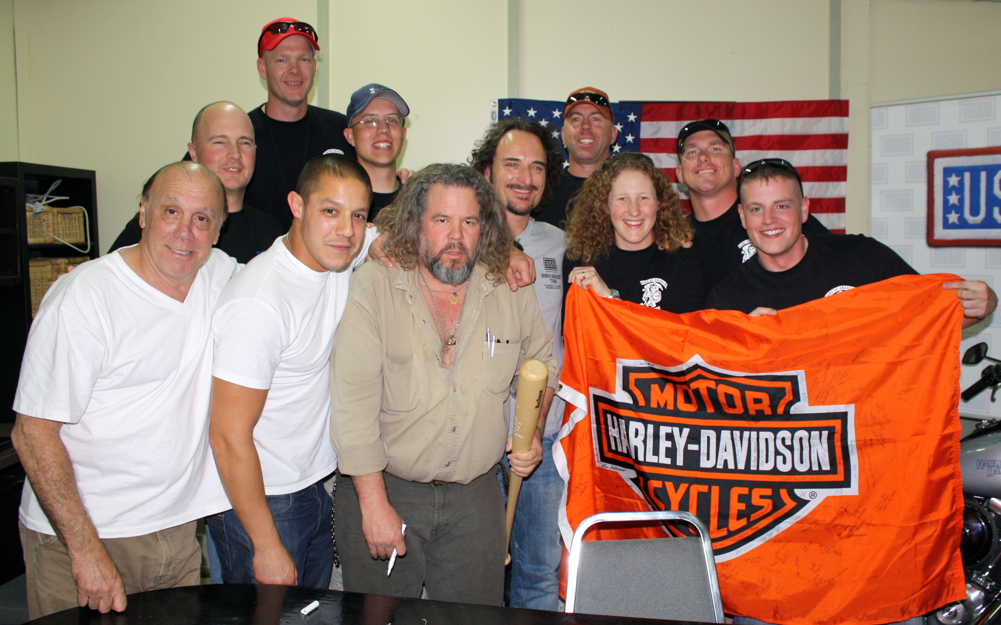 Sons of Anarchy cast members show off a Harley Davidson banner with