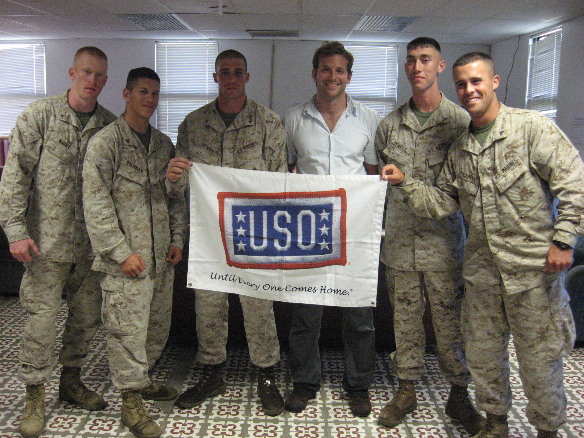 Actor Bradley Cooper takes a moment to pose with service members stationed in Guantanamo Bay, Cuba, during a week-long USO tour in 2008.  Cooper was in the region on his first tour to show support to U.S. troops and bring them a touch of home.