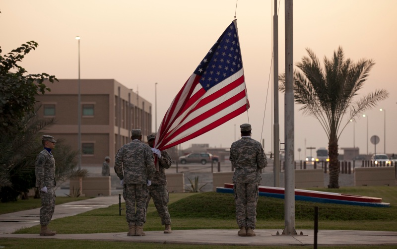 Soldiers remove the US flag at Camp Arafjon