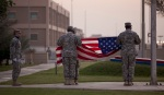 Soldiers fold the US flag at Camp Arafjon