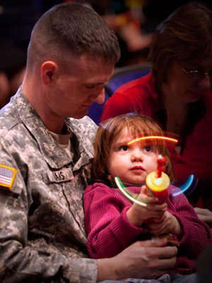 Maj John Haas and his daughter Isabella, 3, wait for the kick off of the fifth installment of The Sesame Street/USO Experience for Military Families at the Franklin County Veterans Memorial in Columbus, Ohio April 14, 2011. (USO Photo by Fred Greaves)
