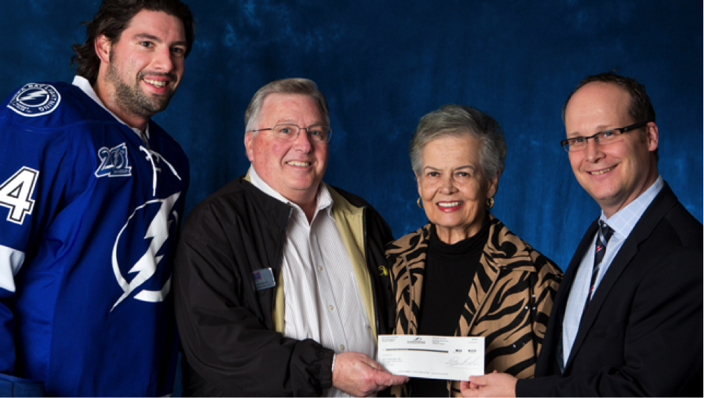 Tampa Bay Lightning player Nate Thompson, left, and Lightning Chief Operating Officer Steve Griggs, right, present a $50,000 check to Walter Lamerton and Brenda Schwarzkopf, the wife of the late General Norman Schwarzkopf. Photo courtesy of the Tampa Bay Lightning