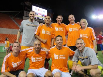 The Coast Guard squad - in orange jerseys - pose with Houston Dynamo players Tally Hall, top left, and Brad Davis, bottom right, after their victory Saturday. USO photo