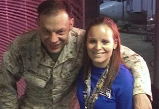 Lindsy Wadas, director of the USO of Illinois' center at Chicago O'Hare International Airport, poses with Marine Maj. Matthew Winkelbauer after he and 12 fellow Marines arrived in Chicago on Monday. The 13 Marines were treated to an inpromptu water-canon salute and gate greeting and all ended up with first class seats on their American Airlines flight to San Diego. Courtesy of USO of Illinois
