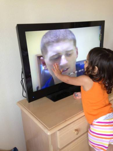 Army Spc. James Gleason's daughter, , touches the television as she watches him read a book to her via a USO/United Through Reading video. Photo courtesy of the Gleason family