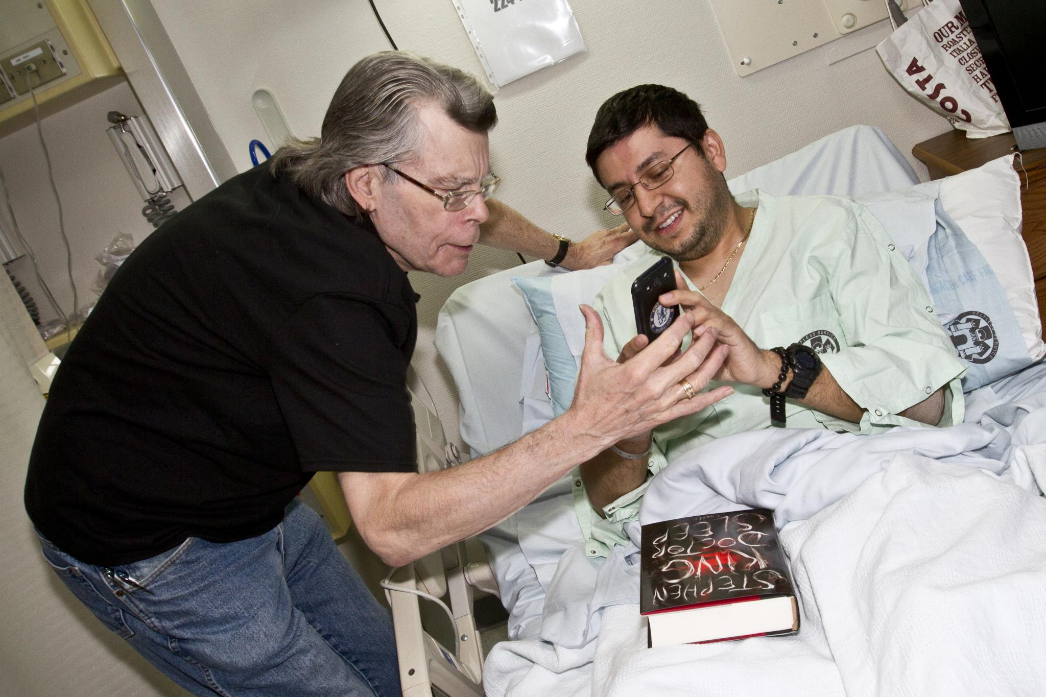 Stephen King shares a moment with Navy Lt. j.g. Pablo Yepez at Landstuhl Regional Medical Center in Germany. USO photo by Mike Clifton