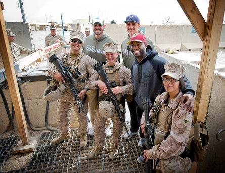 From left to right, NFL stars Brandon Fields, Jimmy Graham and Pierre Garcon pose for a photo with troops during their USO tour to the Middle East in March. USO photo by Dave Gatley
