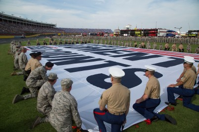Service members unfurl a section of the USO's Every Moment Counts flag before the start of the Coca-Cola 600 in Charlotte, North Carolina, in May. USO photo by Joseph Andrew Lee