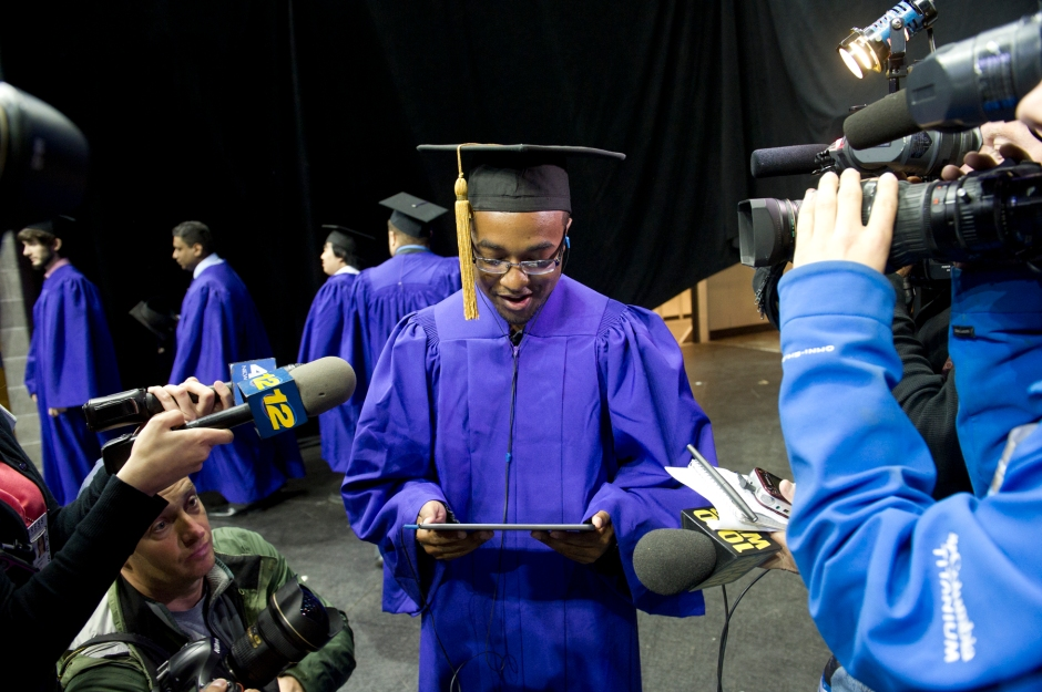 Pedro Cruz III watches a video message from his father on iPad moments after graduating from New York University on May 23. Cruz's father, New York Army National Guard Staff Sgt. Pedro Cruz Jr., is deployed to Kuwait and was unable to attend the ceremony, but he worked with the USO to figure out how he could be the first to congratulate his son. NYU Polytechnic School of Engineering photo by Elena Olivo