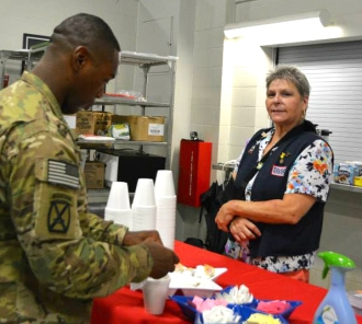 USO volunteer Alice Barton mans the snack table as troops wait for their welcome home ceremony July 15 in Fort Drum, N.Y. USO photo