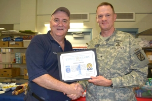 George Barton receives a certificate of appreciation for his USO volunteerism at welcome home events from Army Brig. Gen. Michael Howard on July 15 in Fort Drum, N.Y. USO photo