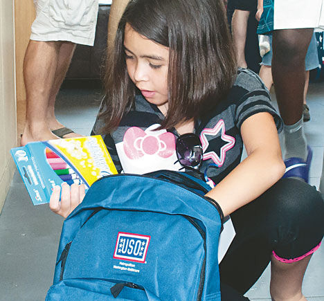 Ashley Sibinski, 10, looks through her new backpack Aug. 2 during the USO of Metropolitan Washington's Operation Back-to-School event at the USO Warrior and Family Center at Fort Belvoir, Virginia. Photo by TD Jackson/Courtesy of the Belvoir Eagle