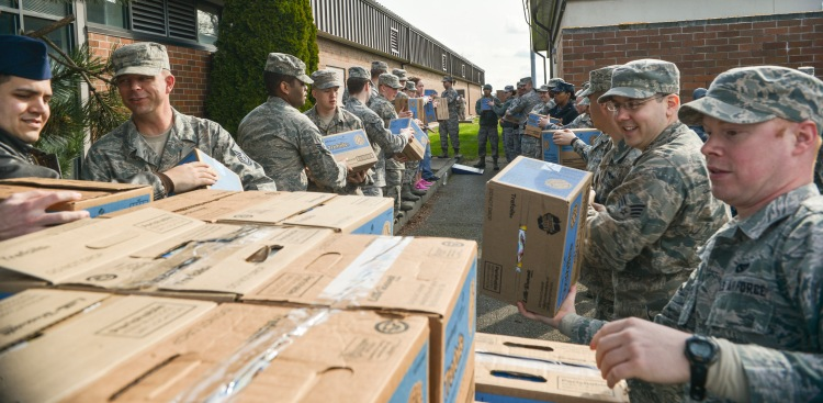 A group of Joint Base Lewis-McChord, Washington-based airmen  help the USO distribute Girl Scout Cookies. Photo courtesy of the Department of Defense