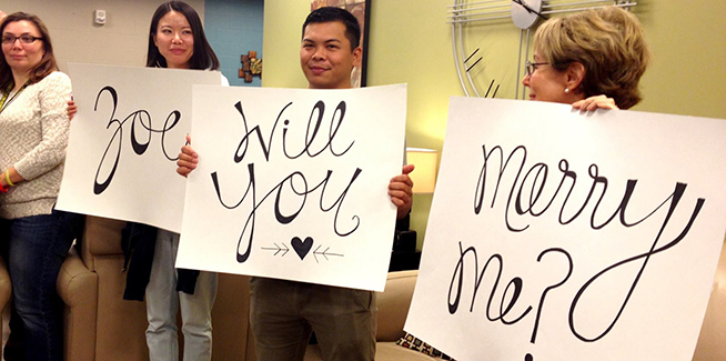 Volunteers hold up signs during the surprise proposal at USO San Antonio. USO photo