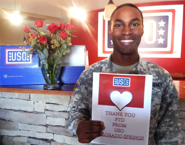 A soldier holds up a sign at USO Colorado Springs. USO photo