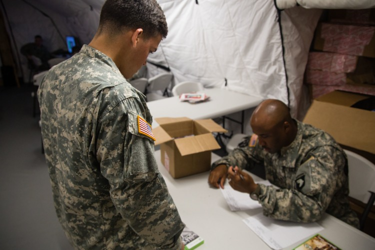Army Pfc. Michael Matale, left, signs out a video game from Sgt. Brandon Banks at the grand opening of the USO at Barclay Training Center in Monrovia, Liberia. Army photo by Spc. Rashene Mincy