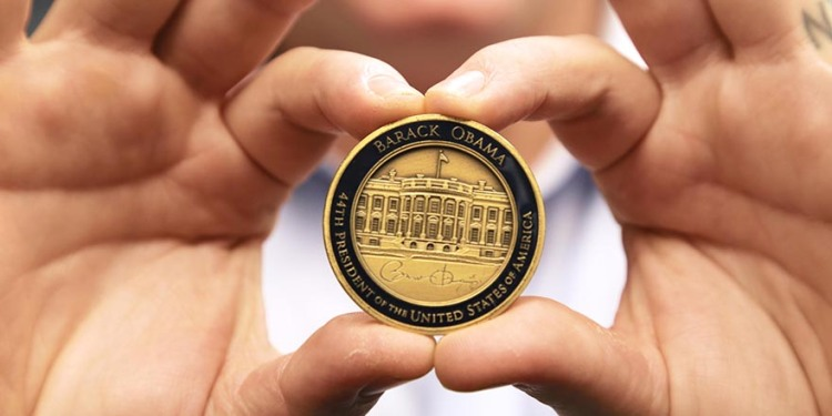 Joseph Andrew Lee holds up the coin President Barack Obama gave him in 2011.
