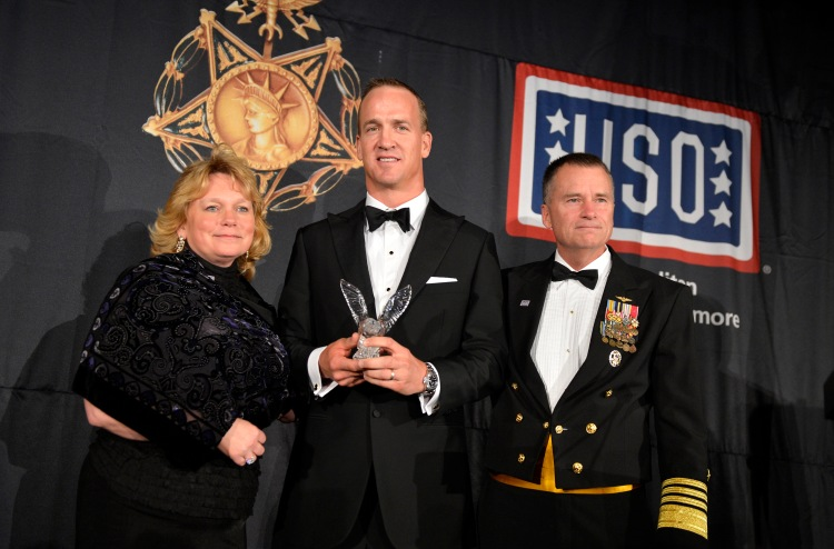 Denver Broncos quarterback Peyton Manning accepts the USO-Metro Merit Award. USO Photo by Mike Theiler