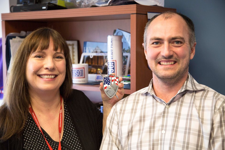 USO Director of Information Technology Val Donegan, left, and USO Director of Logistics and Facilities Jonathan Matthews hold up a coin they both received in 2012 for their work building the USO Warrior and Family Center on Fort Belvoir, Virginia.