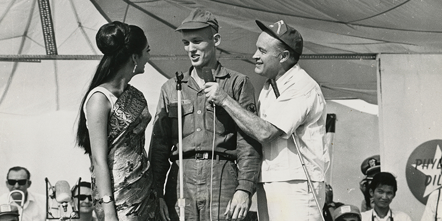 Bob Hope interviews a service member on stage in Vietnam in 1966. USO photo