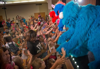 The cast of the Sesame Street/USO Experience for Military Families shakes hands with young audience members. USO Photo by Dave Gatley