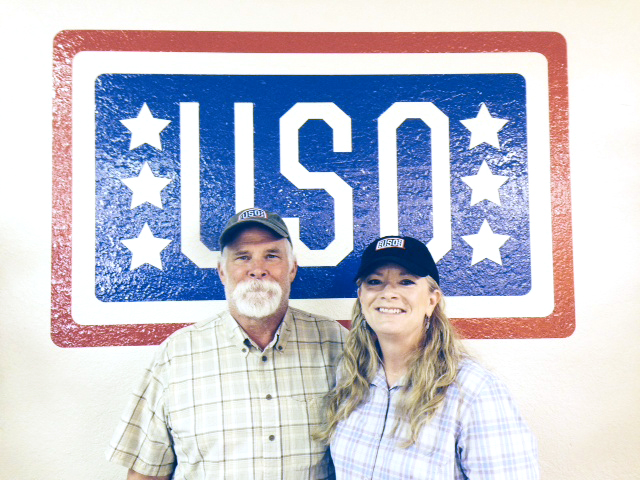 The Mezzapelles pose in front of the USO logo. Photo courtesy Chris Mezzapelle