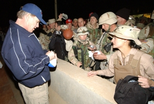 John Elway autographs a football during a 2004 USO tour stop in Iraq. DOD photo