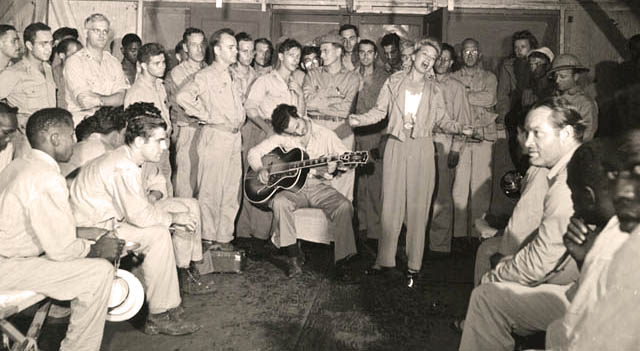 Guitarist Tony Romano accompanies Frances Langford in an impromptu performance in 1944 as Bob Hope, lower right, looks on. Library of Congress