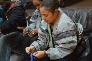 Service members craft bracelets at USO Camp Buehring.