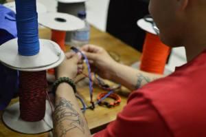 A service member crafts a bracelet.